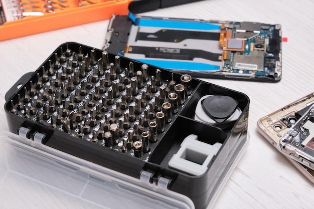 Ensemble d'embouts de tournevis dans une boîte noire, gants, outils pour remplacer le verre du téléphone et de la tablette