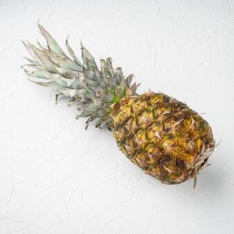 Ensemble entier d'ananas, sur fond de table en pierre blanche, vue de dessus à plat, format carré