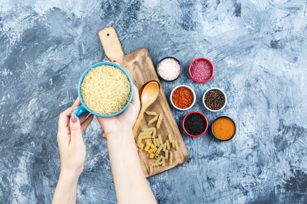 Ensemble d'épices, cuillères en bois et main tenant un bol de pâtes sur fond de plâtre et planche à découper. vue de dessus.