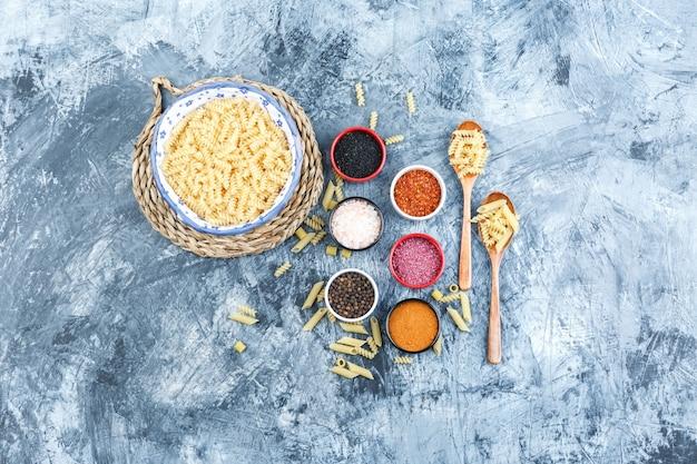 Ensemble d'épices, cuillères en bois et pâtes fusilli dans un bol sur fond de plâtre et de napperon en osier gris. vue de dessus.