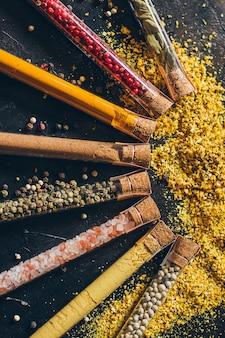 Un ensemble d'épices dans de petits pots avec des couvercles en liège. sel rose, gingembre, curcuma, masala, paprika, paprika fumé. épices sur une surface noire.