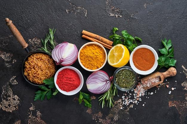 Ensemble d'épices et d'herbes parfumées indiennes sur fond noir en pierre. curcuma, aneth, paprika, cannelle, safran, basilic et romarin dans une cuillère. vue de dessus. maquette.