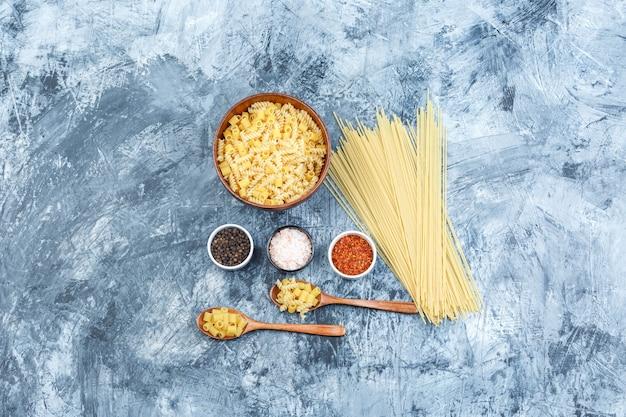 Ensemble d'épices et de pâtes assorties dans un bol et cuillères en bois sur un fond de plâtre grungy. pose à plat.