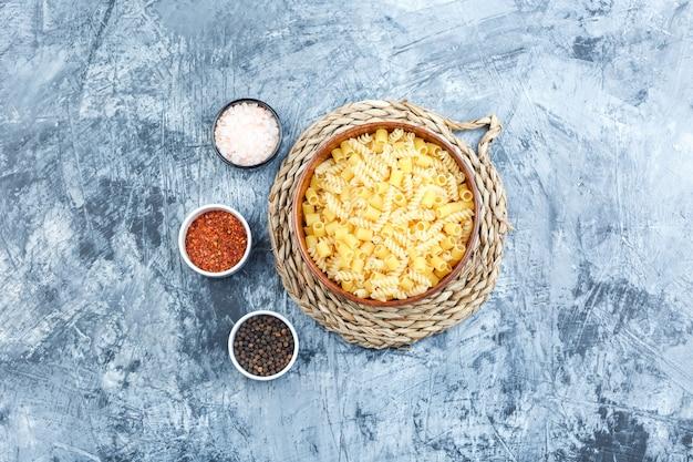 Ensemble d'épices et de pâtes assorties dans un bol sur fond de plâtre et de napperon en osier gris. vue de dessus.