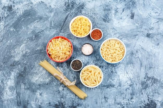 Ensemble d'épices et de pâtes assorties dans des bols sur un fond de plâtre grungy. pose à plat.