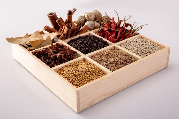 Ensemble d'épices (poivre, poivre blanc, poivre noir, anis, cumin) dans une boîte en bois.