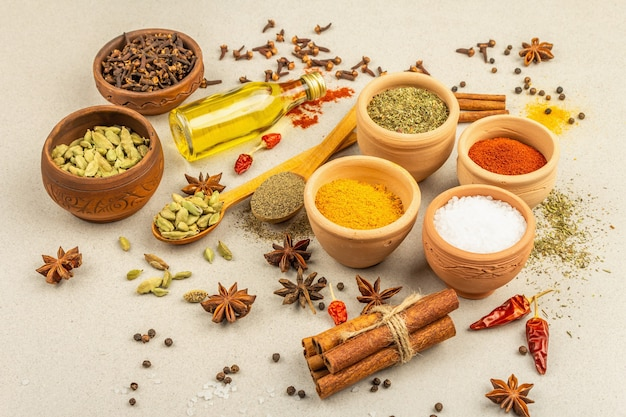 Un ensemble d'épices pour la cuisson du curry. condiments aromatiques : curcuma, paprika, cardamome, cannelle, badiane, piment, poivre noir, herbes sèches, sel. fond de béton clair en pierre, gros plan
