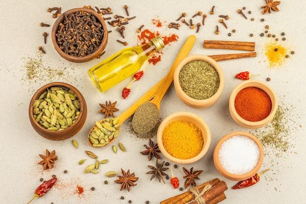 Un ensemble d'épices pour la cuisson du curry. condiments aromatiques : curcuma, paprika, cardamome, cannelle, badiane, piment, poivre noir, herbes sèches, sel. fond de béton en pierre clair, vue de dessus