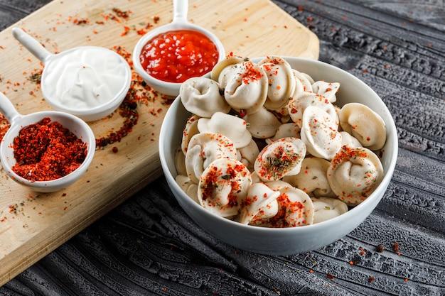 Ensemble d'épices rouges sur une planche à découper et de la pâte dans un bol sur une surface en bois grise. vue grand angle.