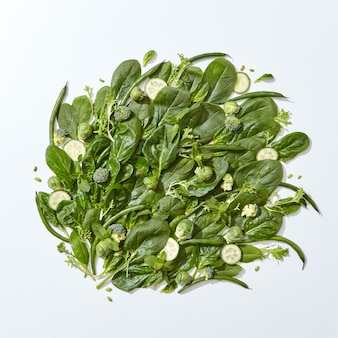 Ensemble d'épinards verts biologiques, feuilles de menthe, brocoli, asperges, choux de bruxelles et tranches de concombre sur fond gris avec un espace pour le texte. nourriture saine végétarienne. mise à plat