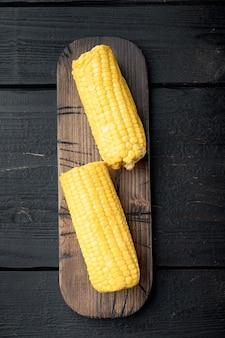 Ensemble d'épis de maïs savoureux, sur fond de table en bois noir, vue de dessus à plat