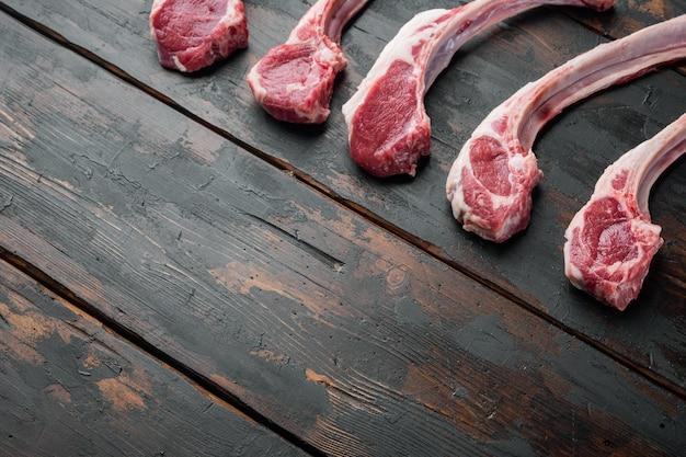 Ensemble d'escalopes de boeuf d'agneau de bouchers crus frais, sur fond de table en bois foncé ancien, avec fond et espace pour le texte