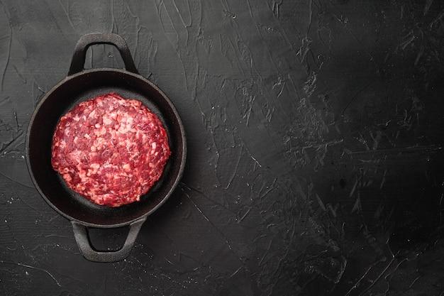 Ensemble d'escalopes de viande hachée de boeuf, sur pierre noire