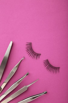 Ensemble d'extensions de faux cils sur fond rose avec une pince à épiler. minimalisme. photo verticale