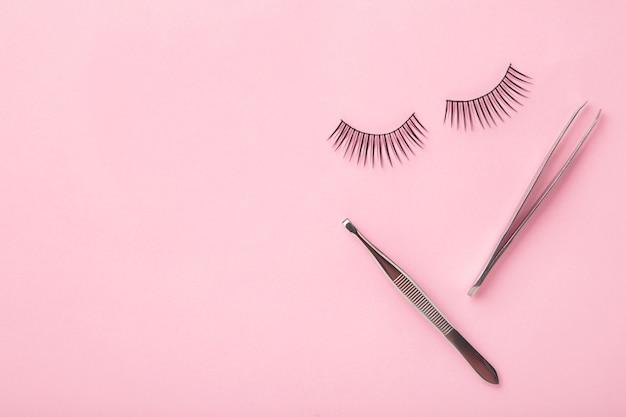 Ensemble d'extensions de faux cils sur fond rose avec une pince à épiler. minimalisme. vue de dessus
