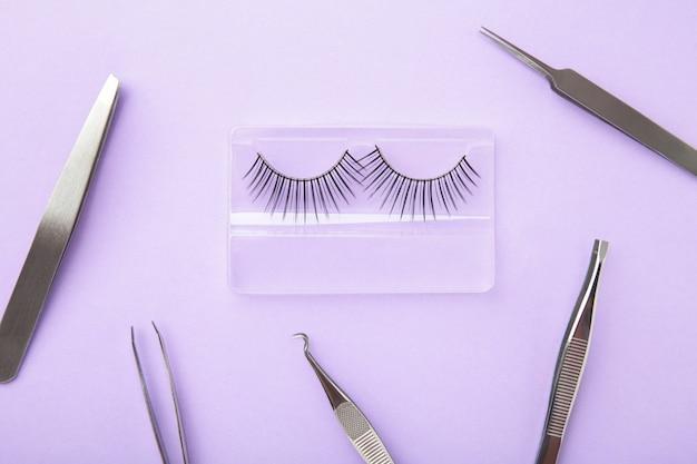 Ensemble d'extensions de faux cils sur fond violet avec une pince à épiler. minimalisme. vue de dessus