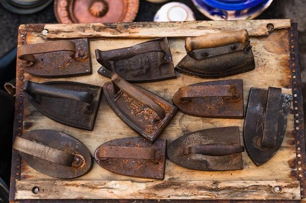 Ensemble de fers en fonte et en acier rouillés sur un marché aux puces