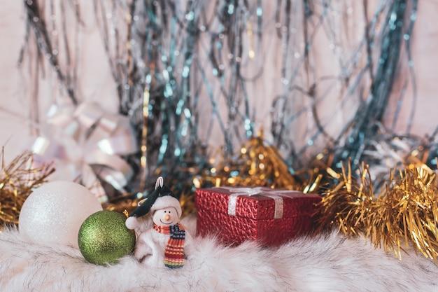 Ensemble festif avec un bonhomme de neige souriant, des cadeaux et des décorations du nouvel an. guirlande de noël en arrière-plan. mise au point sélective au premier plan.
