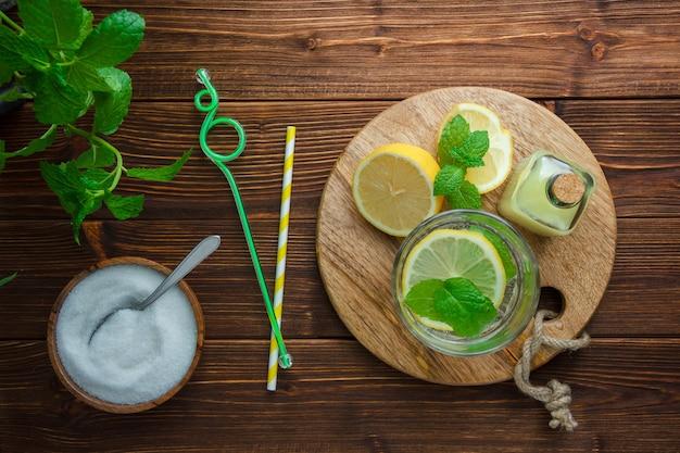 Ensemble de feuilles, couteau en bois, planche à découper, bol de sel et moitié de citron sur une surface en bois. vue de dessus.