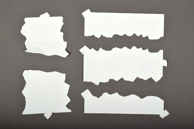 Ensemble de feuilles de papier déchirées avec des autocollants isolés sur fond gris