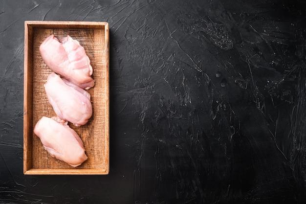 Ensemble de filet de viande de poulet cru, dans une boîte en bois, sur pierre noire