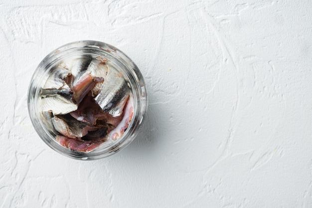 Ensemble de filets d'anchois salés, dans un bocal en verre, sur blanc