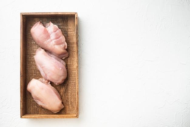 Ensemble de filets de poitrine de poulet, dans une boîte en bois, sur pierre blanche