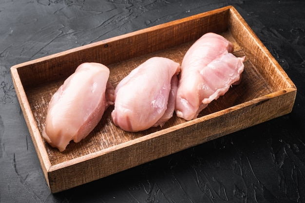 Ensemble de filets de poitrine de poulet, dans une boîte en bois, sur pierre noire