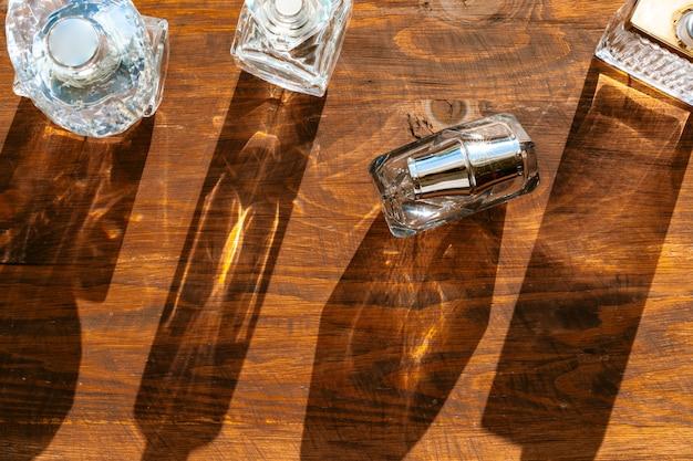 Ensemble de flacons de parfum sur une lumière vive avec des ombres