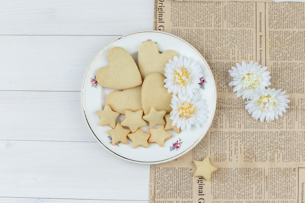 Ensemble de fleurs et de biscuits dans une assiette sur fond en bois et journal. pose à plat.
