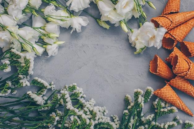Ensemble de fleurs et cornet de crème glacée sur gris blanc. vue de dessus.