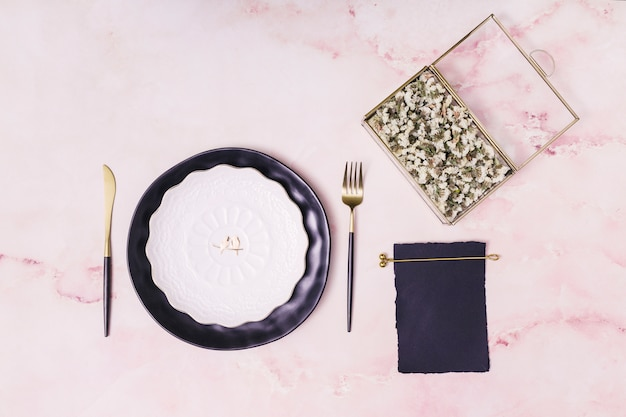 Ensemble de fleurs dans une boîte et du papier près d'une assiette et des couverts