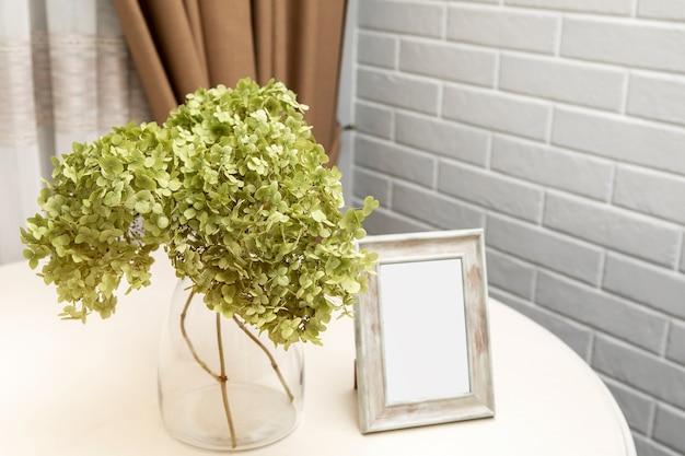 Ensemble de fleurs d'hortensia et cadres photo vierges sur table en bois blanc