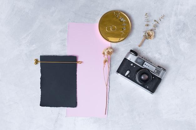 Ensemble de fleurs près de papiers, anneaux sur appareil photo rond et rétro