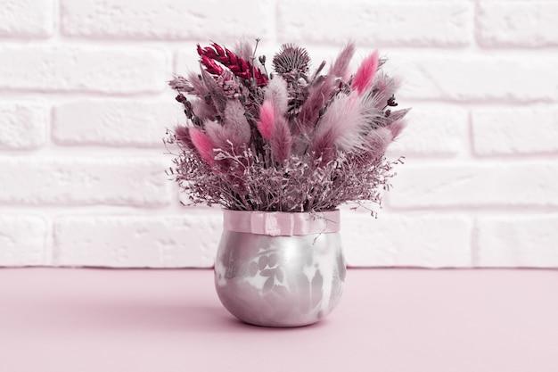Ensemble de fleurs séchées à la main de couleur rose. bouquet de branche naturelle, blé, plantes, herbe sauvage. composition floristique sur fond de décor de briques blanches.