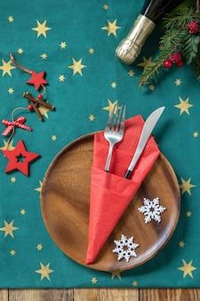 Ensemble de fourchette et couteau de table avec serviette en papier rouge et branche de sapin sur une table de fête rustique vue de dessus