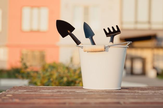 Ensemble de fournitures de jardinage dans un seau blanc sur fond de nature. articles ménagers pour le jardin. outils de jardin, râteau, pelles. les articles ménagers sont rassemblés en tas.