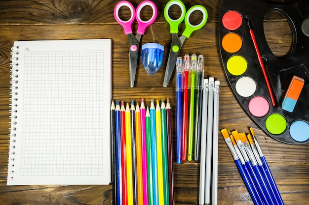 Ensemble de fournitures de papeterie scolaire. cahier vierge, crayons de couleur, stylos, aquarelles, ciseaux et autres objets sur un bureau en bois. retour au concept de l'école