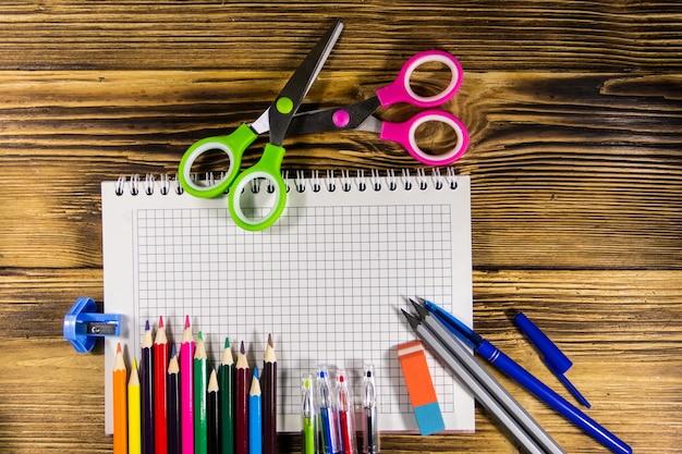 Ensemble de fournitures de papeterie scolaire. cahier vierge, crayons de couleur, stylos, ciseaux, gomme sur un bureau en bois. retour au concept de l'école