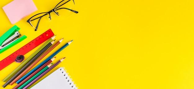 Ensemble de fournitures scolaires sur fond jaune.