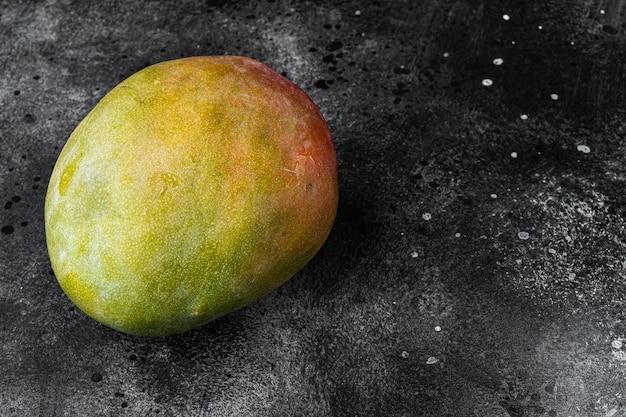 Ensemble de fruits entiers à la mangue, sur fond de table en pierre noire noire, avec espace de copie pour le texte