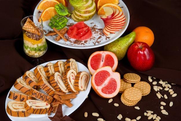 Ensemble de fruits sucrés et un gâteau sur un fond sombre