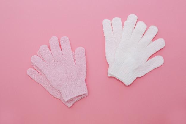 Ensemble de gant de massage exfoliant pour douche sur fond rose. gants à utiliser sous la douche pour massage et gommage.