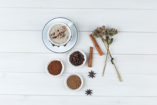 Ensemble de grains de café, café moulu, épices, biscuits, herbes séchées et café dans une tasse sur un fond en bois. vue de dessus.