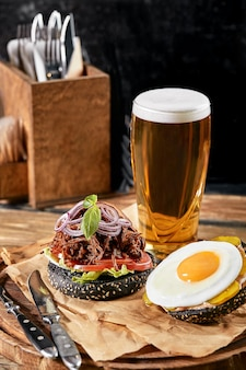 Ensemble de hamburger avec oeuf et bière. un ensemble standard de boissons et de nourriture dans le pub, de la bière et des collations.