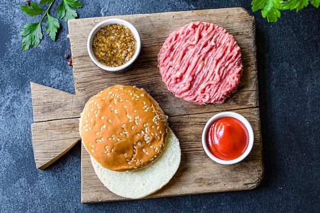Ensemble de hamburgers crus viande d'escalope, rouleau, sauce et plus