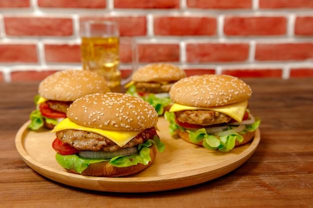 Ensemble de hamburgers de porc et de frites sur un plateau en bois devant le mur de briques.