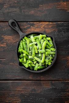 Ensemble de haricots verts surgelés, dans une poêle en fonte, sur fond de table en bois sombre, vue de dessus à plat