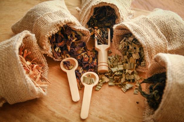 Ensemble d'herbes thaïlandaises dans un sac brun, plusieurs sacs avec une cuillère posée sur le plancher de bois