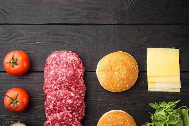 Ensemble d'ingrédients de burger de boeuf, sur fond de table en bois noir